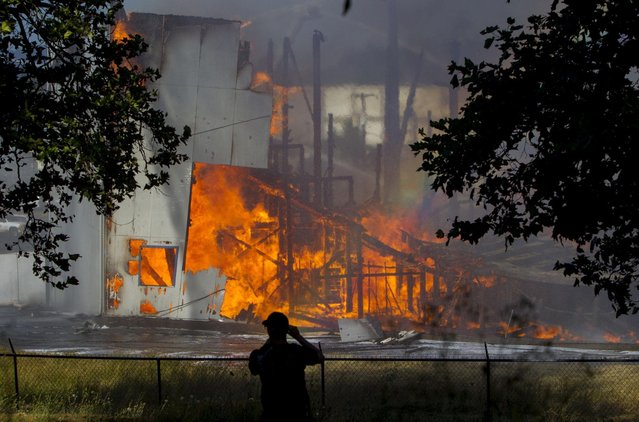 A firefighter films the Civic Stadium burning in Eugene, Ore., Monday, June 29, 2015. The stadium was approved by voters in 1938 during the Great Depression and opened that same year. (Photo by Andy Nelson/The Register-Guard via AP Photo)