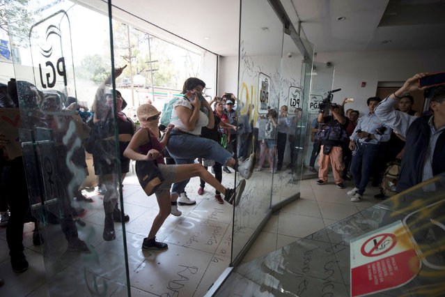 Demonstrators kick a glass door outside Mexico City's attorney general's office in Mexico City, Mexico on August 12, 2019, after local media reported that a teenage girl had been raped by four police officers. (Photo by Reuters/Stringer)
