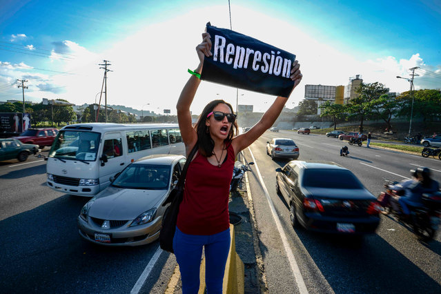 "A student shouts slogans against Venezuelan President Nicola Maduro during a protest on the main highway in Caracas on March 30, 2017. Venezuela' s Supreme Court took over legislative powers Wednesday from the opposition- majority National Assembly, whose speaker accused leftist President Nicolas Maduro of staging a ""coup"". (Photo by Juan Barreto/AFP Photo)"