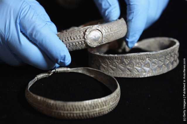 An employee of the British Museum examines a silver arm-rings dating from 900 AD which are part of the Silverdale Viking Hoard