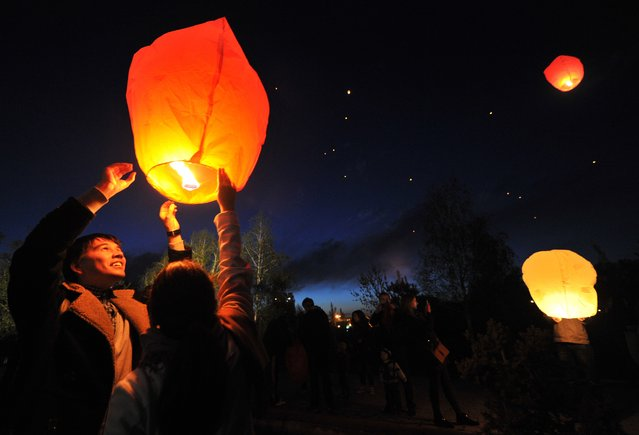 Kyrgyz people release a candle-lit paper lamp into the sky, in Kyrgyzstan's capital Bishkek on April 26, 2014. (Photo by Vyacheslav Oseledko/AFP Photo)