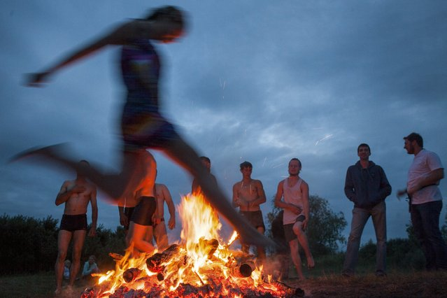 A woman jumps over a campfire during a celebration of the traditional Ivana Kupala (Ivan the Bather) holiday near Omsk, Russia, July 9, 2015. The ancient tradition, originating from pagan times, is usually marked with grand overnight festivities. During the Ivana Kupala, people jump over burning campfires and bathe in a lake or a river, as they believe it will purge them of their sins and make them healthier. (Photo by Dmitry Feoktistov/Reuters)