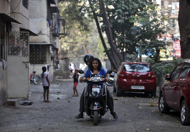 Bharat Makwana (C) teaches his daughter Mansi, 17, how to ride a scooter at a residential area in Mumbai February 5, 2014. (Photo by Mansi Thapliyal/Reuters)