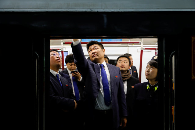 "People travel on a train stopping at a subway station visited by foreign reporters in central Pyongyang, North Korea on April 14, 2017. The Pyongyang Metro consists of two lines: the Chollima Line, which runs north from Puhŭng Station on the banks of the Taedong River to Pulgŭnbyŏl Station, and the Hyŏksin Line, which runs from Kwangbok Station in the southwest to Ragwŏn Station in the northeast. The two lines intersect at Chŏnu Station. Daily ridership is estimated to be between 300,000 and 700,000. Construction of the metro network started in 1965, and stations were opened between 1969 and 1972 by former president Kim Il-sung. Most of the 16 public stations were built in the 1970s, except for the two most grandiose stations – Puhoong and Yonggwang, which were constructed in 1987. In 1971, there was a major accident during the construction of a tunnel under the Taedong River for the Ponghwa Station. Some sources say at least 100 workers died in the accident. This particular section of tunnel was never completed; the metro network is now completely located on the western side of the river. China had provided technical aid for the metro's construction, sending experts to install equipment made in China, including electrical equipment made in Xiangtan, Hunan and the escalator with vertical height of 64m made in Shanghai. Pyongyang Metro is among the deepest metros in the world, with the track at over 110 metres (360 ft) deep underground; the metro does not have any above-ground track segments or stations. Due to the depth of the metro and the lack of outside segments, its stations can double as bomb shelters, with blast doors in place at hallways. It takes three and a half minutes from the ground to the platform by escalator. The metro is so deep that the temperature of the platform maintains a constant 18 °C (64 °F) all year. The Saint Petersburg Metro also claims to be the deepest, based on the average depth of all its stations. The Arsenalna station on Kiev Metro's Sviatoshynsko-Brovarska Line is currently the deepest station in the world at 105.5 metres (346 ft). The Porta Alpina railway station in Switzerland was supposed to be 800 m underground, but the project was indefinitely shelved in 2012. The Pyongyang Metro was designed to operate every few minutes. During rush hour, the trains can operate at a minimum interval of two minutes. The trains have the ability to play music and other recordings. The Pyongyang Metro is one of the cheapest in the world to ride, at only five won (about 0.01 USD) per ticket. Instead of paper tickets, the Metro previously used an aluminium token, with the emblem of the Metro minted on it and the Korean ""지"". It now uses a paper ticket system, with ""지"" printed on it. Smoking and eating inside the Metro system is prohibited and is punishable by a large fine. (Photo by Damir Sagolj/Reuters)"