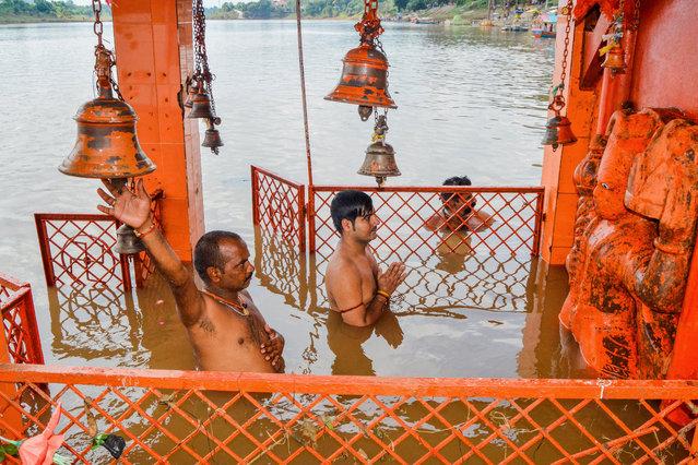 Hindu devotees worship a statue of Lord Hanuman in a flooded temple as water levels of Narmada river rise in Jabalpur, Madhya Pradesh on September 23, 2019. (Photo by Uma Shankar Mishra/AFP Photo)