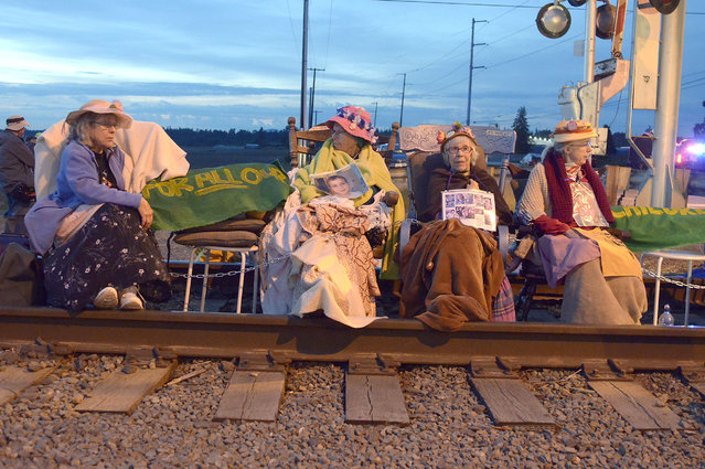 Members of the Seattle Raging Grannies sit in their rocking chairs chained together on the Burlington-Northern Railroad tracks at Farm to Market Road in Skagit County on Friday evening, May 13, 2016, in Burlington, Wash.  From left are Deejay Sherman Peterson, Anne Thureson, Shirley Morrison and Rosy Betz-Zall. Hundreds of people in kayaks and on foot are gathering at the site of two oil refineries in Washington state to call for action on climate change and a fair transition away from fossil fuels. (Photo by Scott Terrell/Skagit Valley Herald via AP Photo)