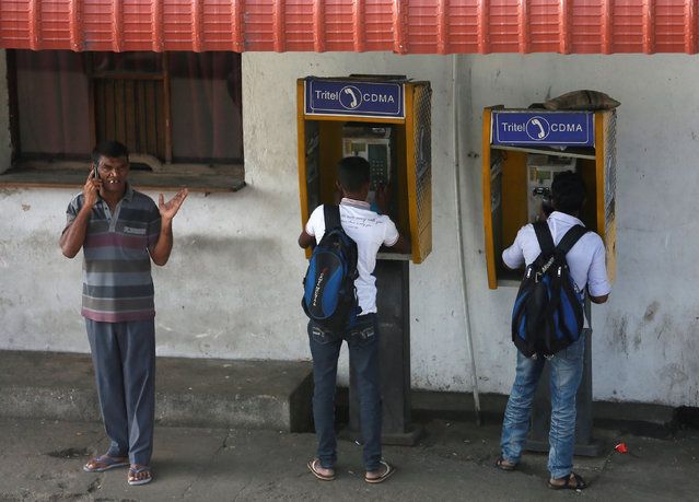 Two boys (R) use public telephones as a man uses his mobile phone next to them near the Fort railway station in Colombo, Sri Lanka February 17, 2017. (Photo by Dinuka Liyanawatte/Reuters)