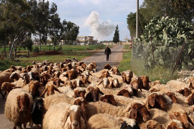 Smoke rises while a man herds sheep after an airstrike on rebel-held Daraa Al-Balad, Syria April 7, 2017. (Photo by Alaa Al-Faqir/Reuters)