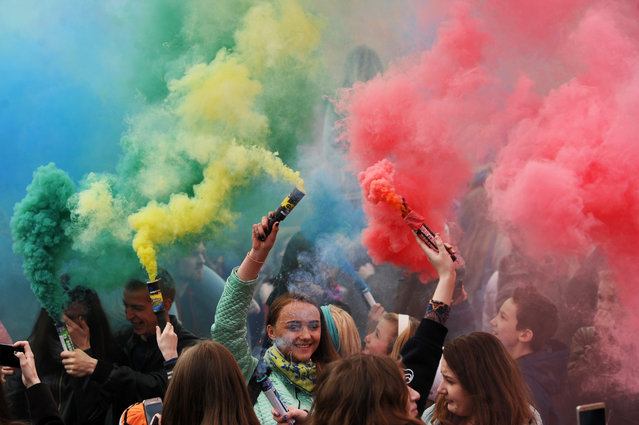 People holding coloured smoke flares take part in a festive event in Minsk on April 30, 2017. (Photo by Sergei Gapon/AFP Photo)
