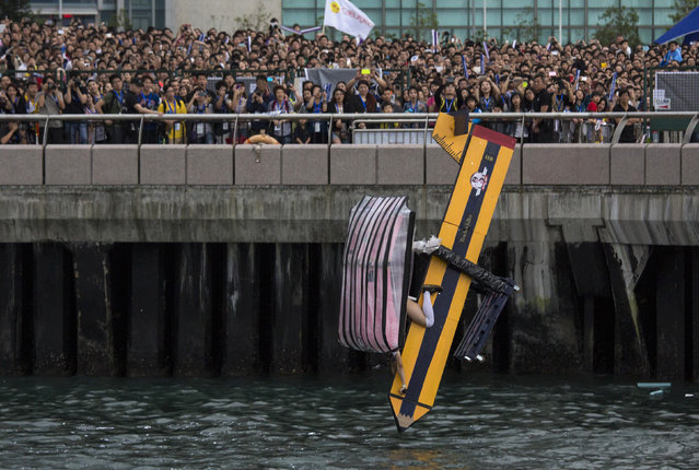 """A participant operates """"Teacher Killer"""", a self-made flying machine, during the Red Bull Flugtag (Flight Day) event at Hong Kong's financial Central district May 11, 2014. Participants from 43 team competed to fly the longest distance in their self-made aircraft in an attempt to win the Flugtag contest. (Photo by Tyrone Siu/Reuters)"""