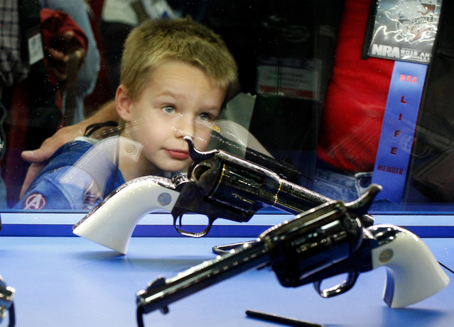 Asher Thomson (5) looks over a pair of Colt revolvers at the National Rifle Association's annual meetings and exhibits show in Louisville, Kentucky, May 21, 2016. (Photo by John Sommers II/Reuters)