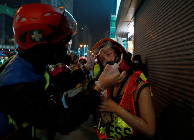 A member of the press affected by the tear gas receives medical attention during an anti-government protest in Hong Kong's tourism district of Tsim Sha Tsui, China on October 27, 2019. (Photo by Ammar Awad/Reuters)