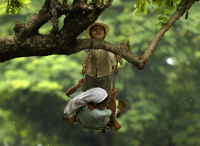 Two kids play on a swing, in Usulutan, 110 km south of San Salvador on July 08, 2015. Government authorities estimate that more than 40,000 farmers – mostly maize growers – have been affected by the drought. (Photo by Marvin Recinos/AFP Photo)