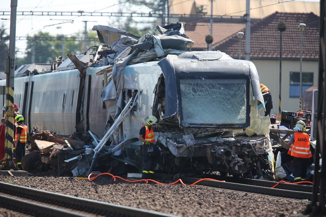 Rescue workers are busy at the scene of a collision between a high-speed train and a truck in the city of Studenka, eastern Czech Republic, Wednesday, July 22, 2015. Two people died in the collision and more than a dozen were injured. (Photo by Petr Sznapka/AP Photo/CTK)