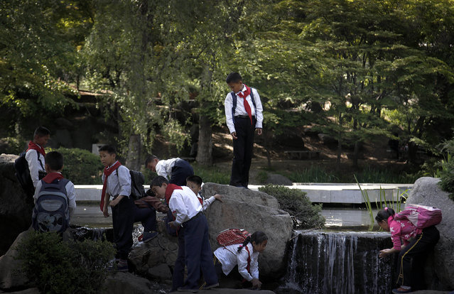 A school boy stands atop a rock and watches his friends wash their hands and face with water from a pond at the Moranbong or Moran Hill, Sunday, May 10, 2015, in Pyongyang, North Korea. The Moran Hill is a popular place for North Koreans to spend their weekends and holidays with family and friends. (Photo by Wong Maye-E/AP Photo)