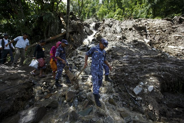 Nepalese police personnel walk along a blocked highway after a landslide at Lumle village in Kaski district July 30, 2015. (Photo by Navesh Chitrakar/Reuters)