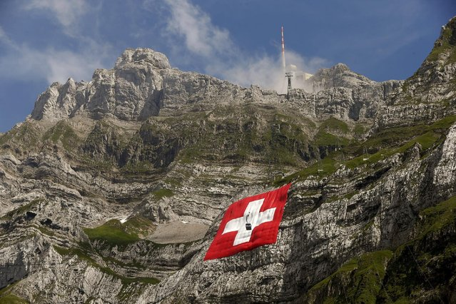 A cablecar descents in front of a huge 80x80 metres (262x262 feet) Swiss national flag on the western face of the north-eastern Swiss landmark Mount Saentis, Switzerland July 31, 2015. The flag marks the Swiss National Day. (Photo by Arnd Wiegmann/Reuters)