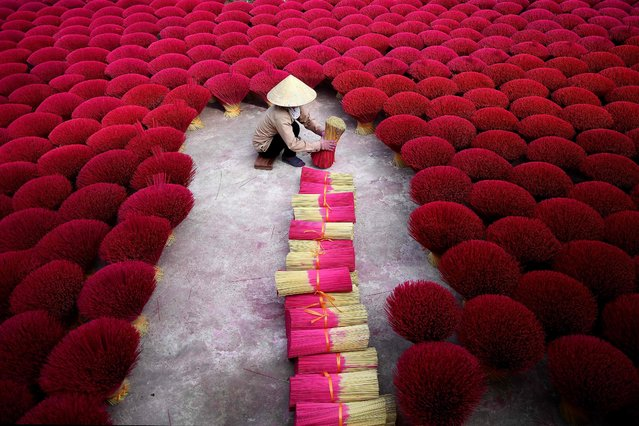"""This picture taken on January 3, 2019 shows a Vietnamese woman collecting incense sticks in a courtyard in the village of Quang Phu Cau on the outskirts of Hanoi. In Vietnam's """"incense village"""", hundreds of workers are hard at work dying, drying and whittling down bamboo bark to make the fragrant sticks ahead of the busy lunar new year holiday. (Photo by Manan Vatsyayana/AFP Photo)"""