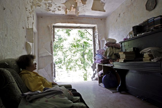 A local resident sits in her damaged flat, which according to locals was hit by recent shelling, in central Horlivka (Gorlovka) in the Donetsk region, Ukraine, August 1, 2015. (Photo by Alexander Ermochenko/Reuters)