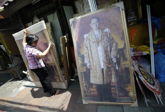 In this Tuesday, June 7, 2016 photo, a shopkeeper places portraits of Thailand's King Bhumibol Adulyadej outside her shop in Bangkok, Thailand. (Photo by Sakchai Lalit/AP Photo)