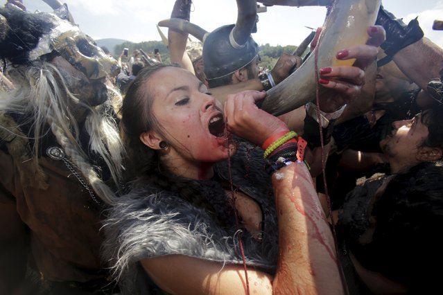 A woman dressed as a Viking drinks local red wine during the annual Viking festival of Catoira in north-western Spain August 2, 2015. (Photo by Miguel Vidal/Reuters)
