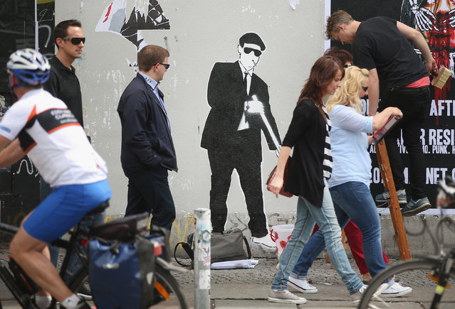 People walk by street art in Kreuzberg district on June 26, 2014 in Berlin, Germany. Berlin, with its long tradition of counter-culture, has become a mecca for street art of all dimensions and messages. (Photo by Sean Gallup/Getty Images)
