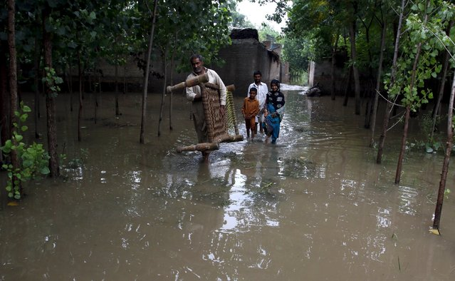 A man and his children walk through a flooded area in Jalabela Village, Peshawar, Pakistan, August 2, 2015. (Photo by Khuram Parvez/Reuters)