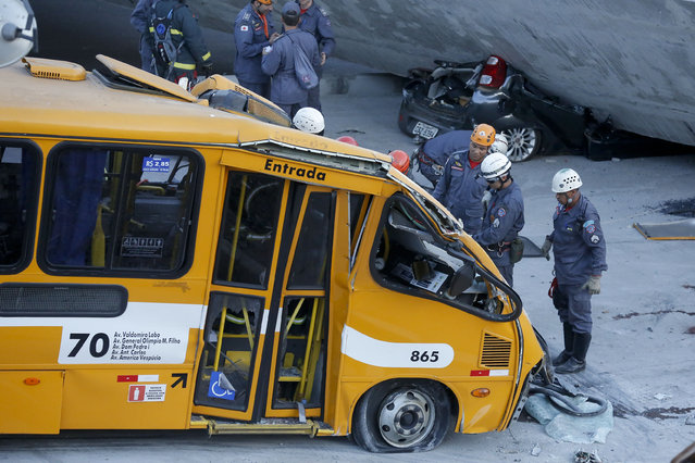 Fire department personnel work to retrieve a body from a bus after retrieving it from underneath a collapsed bridge in Belo Horizonte, Brazil, Thursday, July 3, 2014. The overpass under construction collapsed Thursday in the Brazilian World Cup host city. The incident took place on a main avenue, the expansion of which was part of the World Cup infrastructure plan but, like most urban mobility projects related to the Cup, was not finished on time for the event. (Photo by Victor R. Caivano/AP Photo)