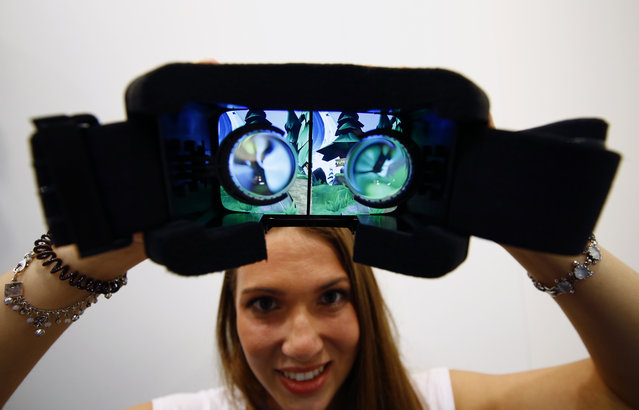 A woman shows VR goggles manufactured by hands-free 3D virtual reality system for smartphones Durivis during the Gamescom 2015 fair in Cologne, Germany August 5, 2015. (Photo by Kai Pfaffenbach/Reuters)