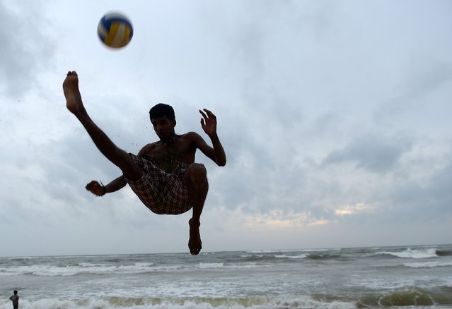 A Sri Lankan youth plays football on a beach in Colombo on July 6, 2014. (Photo by Lakruwan Wanniarachchi/AFP Photo)