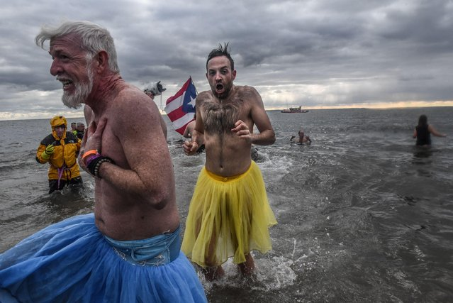 People run into the Atlantic ocean during the annual Polar Bear plunge at Coney Island in New York, January 1, 2020. (Photo by Stephanie Keith/Reuters)