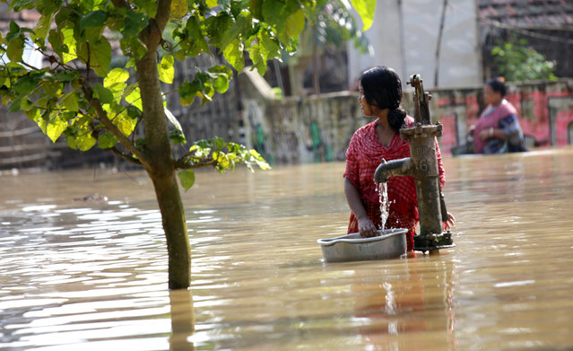A photo made avialable on 05 August 2015 shows an Indian woman collecting drinking water from a water pump in the submerged village of Sreerampur, some 150 kilometers north of Calcutta, India, on 04 August 2015. At least 215 people have died in floods and a landslide following monsoon rains in India over the past week, 83 deaths were reported from the western state of Gujarat and 69 from eastern West Bengal. The worst-affected states were West Bengal, Gujarat and Rajasthan, the Home Ministry said. (Photo by Piyal Adhikary/EPA)