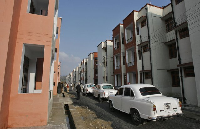 Bullet-proof Ambassador cars, manufactured by Hindustan Motors, which are used by the government officials, are parked beside newly constructed flats built for Kashmiri Hindu or Pandit migrants during the inauguration ceremony of the Jagti Township on the outskirts of Jammu March 4, 2011. (Photo by Mukesh Gupta/Reuters)