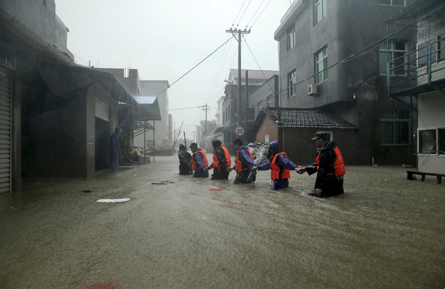 Rescue workers walk on a flooded street at a town hit by Typhoon Soudelor in Ningde, Fujian province, China, August 9, 2015. (Photo by Reuters/Stringer)