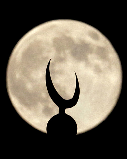 """A perigee moon, also known as a supermoon, looks over a crescent of a minaret of grand Faisal mosque in Islamabad, Pakistan, Saturday, July 12, 2014. The phenomenon, which scientists call a """"perigee moon"""", occurs when the moon is near the horizon and appears larger and brighter than other full moons. (Photo by Anjum Naveed/AP Photo)"""