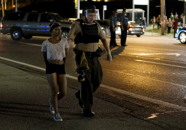 A police officer holds a protester who was detained in Ferguson, Missouri, August 10, 2015. Protesters regrouped in Ferguson, Missouri, on Monday evening after a state of emergency was declared, aimed at preventing a repeat of violence the night before on the anniversary of the police shooting of unarmed black man Michael Brown. (Photo by Rick Wilking/Reuters)