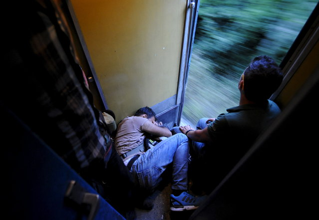 A migrant sleeps on a train as it travels through Macedonia July 31, 2015. (Photo by Ognen Teofilovski/Reuters)