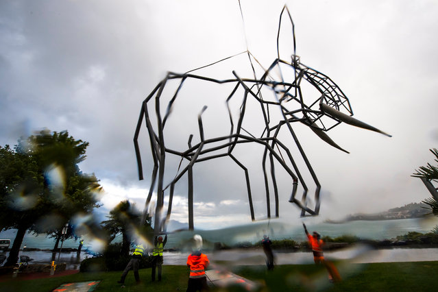 A sculpture shaped like an elephant, created by Swiss artist Dominique Andreae, is placed onto a base with a Super Puma helicopter prior to the start of the fifth Biennale of sculptures in Montreux, Switzerland, 25 July 2017. The elephant is made of steel and is 12 meters high, 15 meters long, 9 meters wide and weighs 3.7 tons. (Photo by Jean-Christophe Bott/EPA)