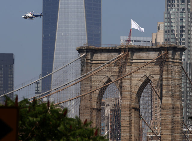 An NYPD helicopter flies over the Brooklyn Bridge inspecting white flags that have been placed on the top, Brooklyn, New York, July 22, 2014. Police are investigating who removed the American Flags and changed them overnight. (Photo by Andrew Gombert/EPA)