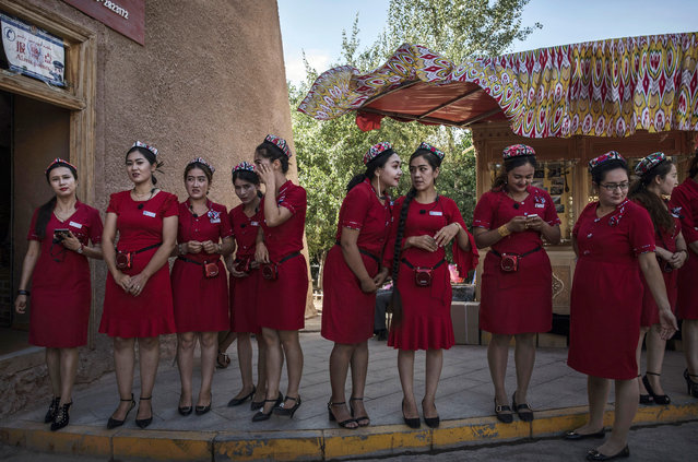 Ethnic Uyghur tourists guides wait to perform in a show for Chinese tourists on June 29, 2017 in the old town of Kashgar, in the far western Xinjiang province, China. (Photo by Kevin Frayer/Getty Images)