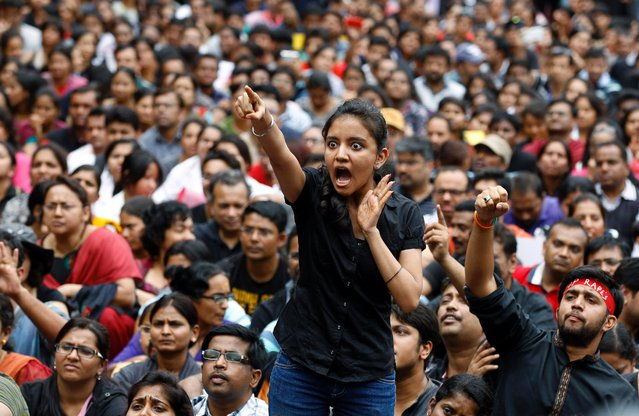 An angry protester points her finger towards the Bangalore police chief during a protest against alleged police inaction after a six-year-old was raped at a school, in Bangalore, India, July 19, 2014. More than 4,000 parents and relatives of children who attend the school shouted slogans against the school's administration July 19, 2014 and demanded that police arrest those involved in the July 2 incident, which was reported only this past week. (Photo by Aijaz Rahi/AP Photo)