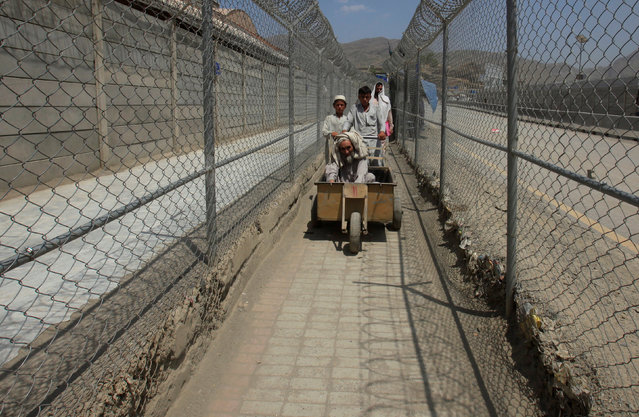 Men coming from Afghanistan move down a corridor between security fences at the border post in Torkham, Pakistan June 18, 2016. (Photo by Fayaz Aziz/Reuters)