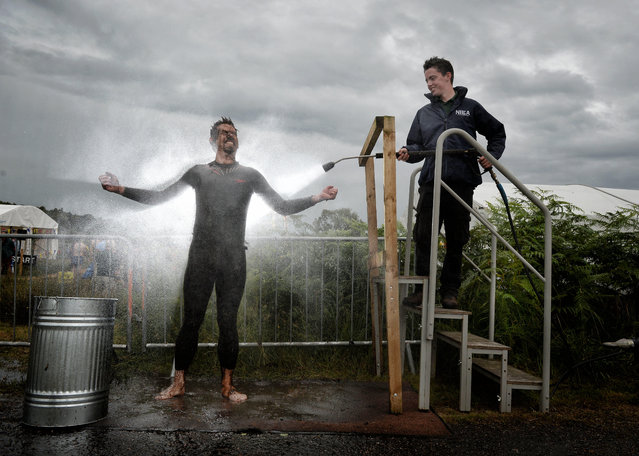 An entrant is hosed down in the 'shower cubicle' after takes part in the Irish Bog Snorkelling championship this afternoon at Peatlands Park on July 27, 2014 in Dungannon, Northern Ireland. The annual event sees male and female competitors swim the 60m length of the bog watched by scores of spectators and takes place on International Bog Day. (Photo by Charles McQuillan/Getty Images)