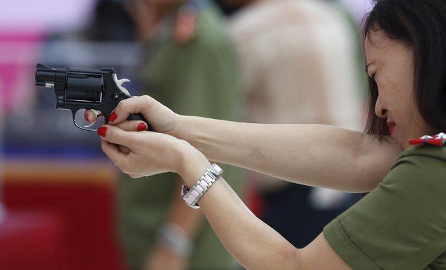 A policewoman demonstrates a Vietnamese-made pistol during celebrations to commemorate the 70th anniversary of the establishment of the Vietnam Public Security police force at the National Convention Center in Hanoi August 18, 2015. (Photo by Reuters/Kham)