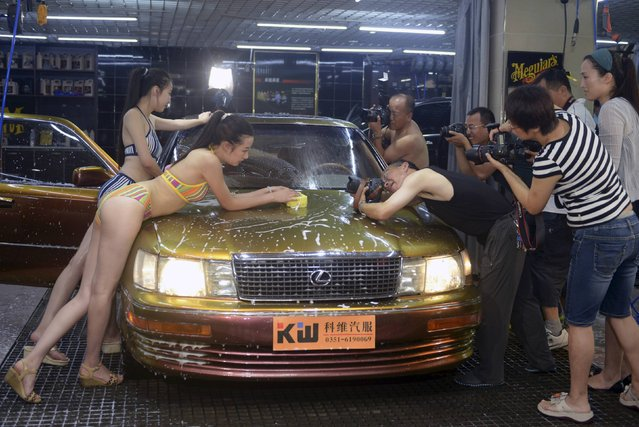 Photographers take pictures as models in bikinis wash a car during a promotional event at an auto service centre in Taiyuan, Shanxi province July 27, 2014. According to local media, the owner of the service centre hired two models to wash a car in bikinis and invited customers to take pictures as part of a promotional campaign, hoping to attract more business. (Photo by Reuters/Stringer)