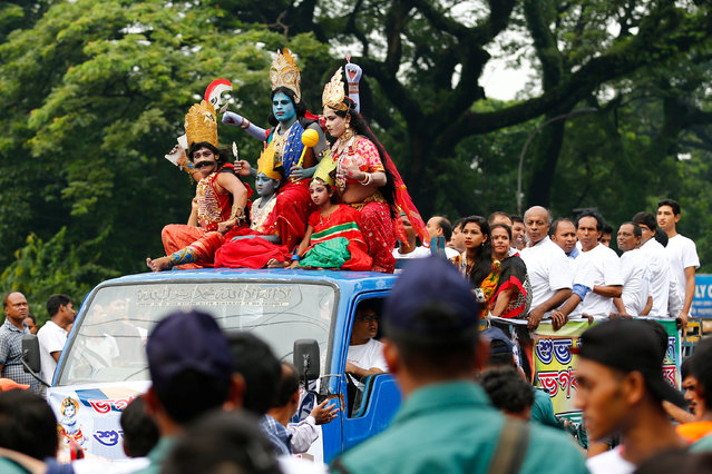 Hindu devotees dressed as different religious figures sit on top of a truck as they celebrate Janmashtami festival, which marks the birth anniversary of Lord Krishna, in Dhaka, Bangladesh, August 14, 2017. (Photo by Mohammad Ponir Hossain/Reuters)