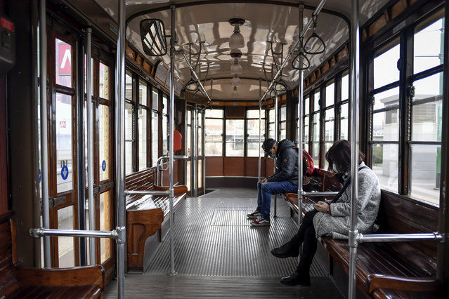 People wear sanitary masks as they ride an empty tram in downtown Milan, Italy, Wednesday, February 26, 2020. Italy has been struggling to contain the rapidly spreading outbreak that has given the country more coronavirus cases outside Asia than anywhere else. (Photo by Claudio Furlan/LaPresse via AP Photo)