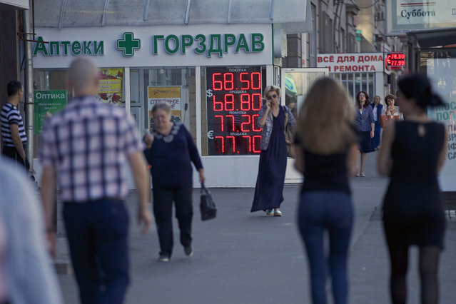 People walk past an exchange office sign showing the currency exchange rates in Moscow, Russia, Friday, August 21, 2015. The Russian ruble currency is falling under the pressure of cheaper oil, reviving concerns over the country's economic outlook. (Photo by Ivan Sekretarev/AP Photo)