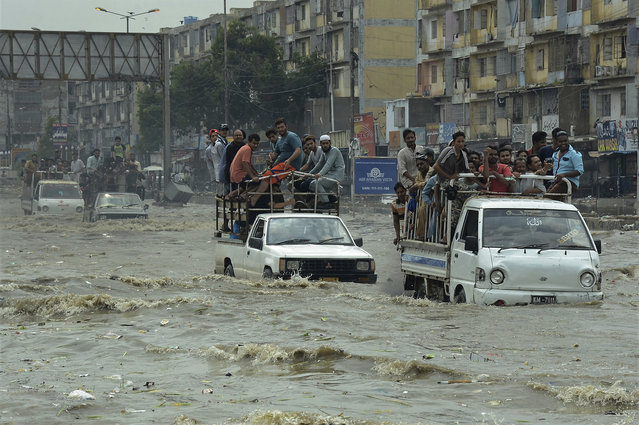 Pakistani commuters travel on a flooded street following a heavy rainfall in Karachi, Pakistan, Thursday, August 31, 2017. Monsoon rains in Pakistan's port city of Karachi left at least eight people dead in flood-related mishaps, officials said Thursday. The destruction came on the heels of days-long downpours in neighboring India that especially caused havoc in Mumbai. (Photo by Shakil Adil/AP Photo)