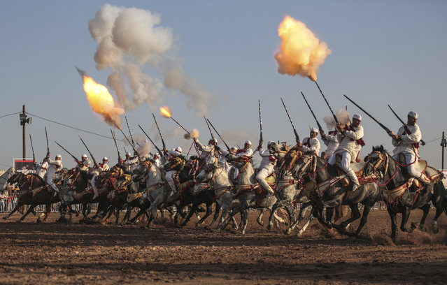 In this Thursday, August 17, 2017 photo, a troupe charges and fires their rifles during Tabourida, a traditional horse riding show also known as Fantasia, in Mansouria, near Casablanca, Morocco. (Photo by Mosa'ab Elshamy/AP Photo)